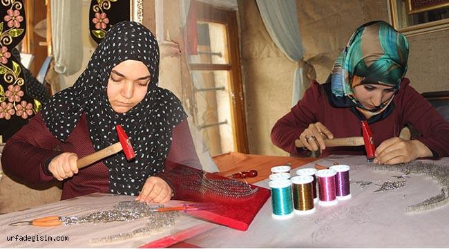 Kadınlar çekiç ve çivi kullanarak resim yapıyor